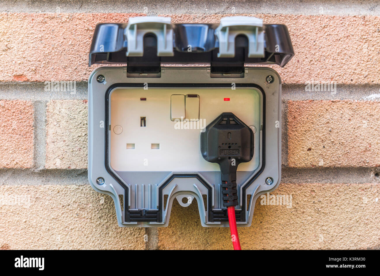 Plug and lead in an outside power supply on a residential house wall, mainly for garden use. Three pin, British, Stock Photo