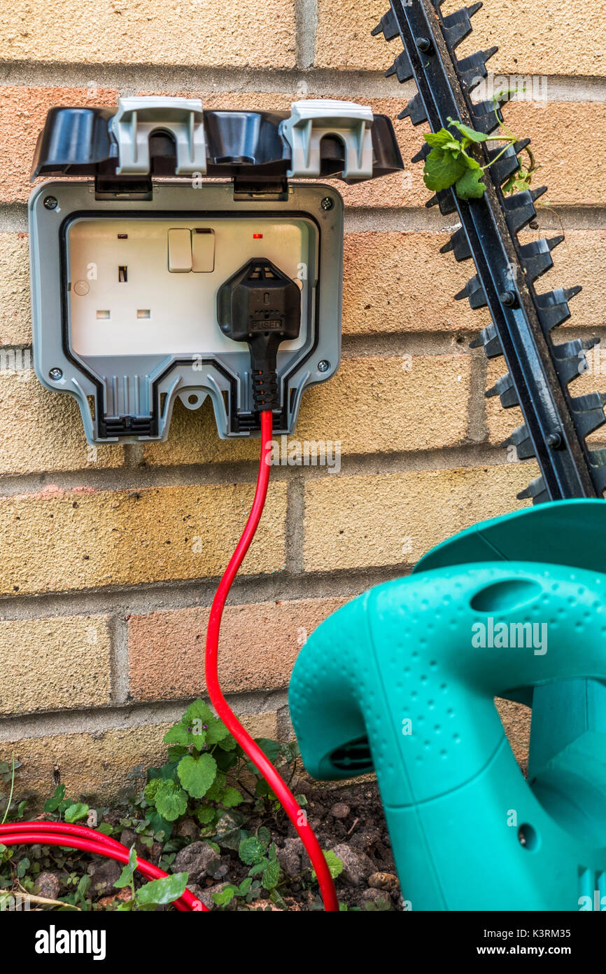 Hedge trimmer plugged into an outside power supply on a residential house wall. Three pin, British, twin electrical Stock Photo