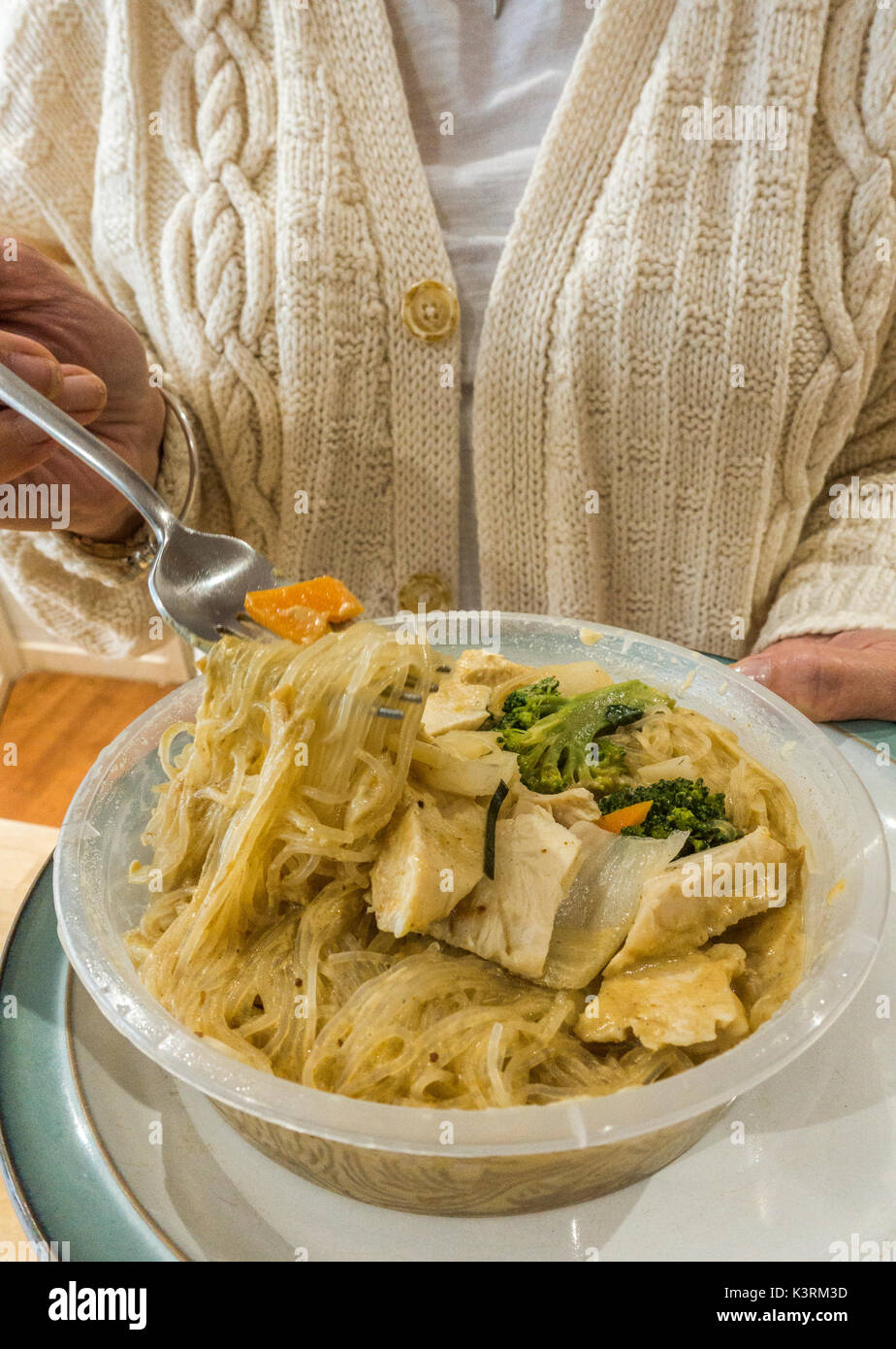 A woman holding a fork and a plate of hot Chinese vegetable noodles in a plastic container, as part of a takeaway meal at home. England, UK. - Stock Image