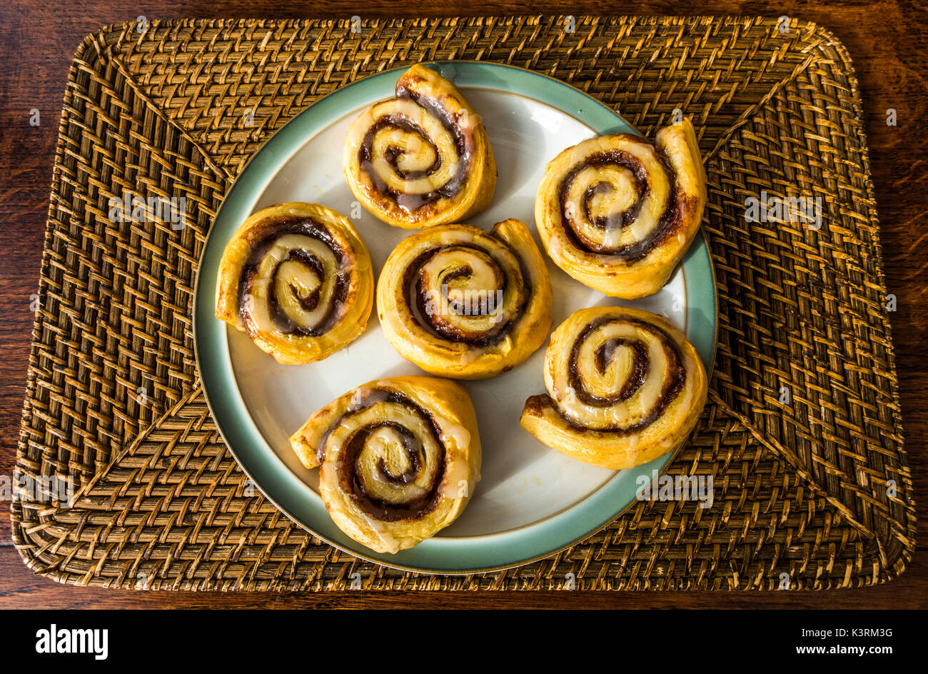 Homemade, oven baked, cinnamon swirls, with melted marmalade and icing sugar topping, laid out on a plate, on a wicker mat, ready to eat. England, UK. - Stock Image