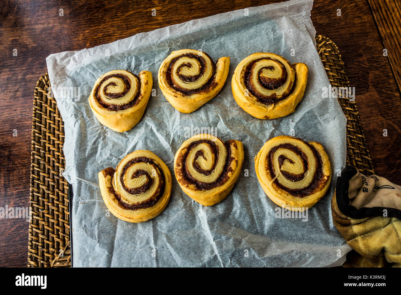 Hot, homemade, cinnamon pastry swirls, straight from the oven, on a grease proof paper tray, held by a padded glove. England, UK. - Stock Image