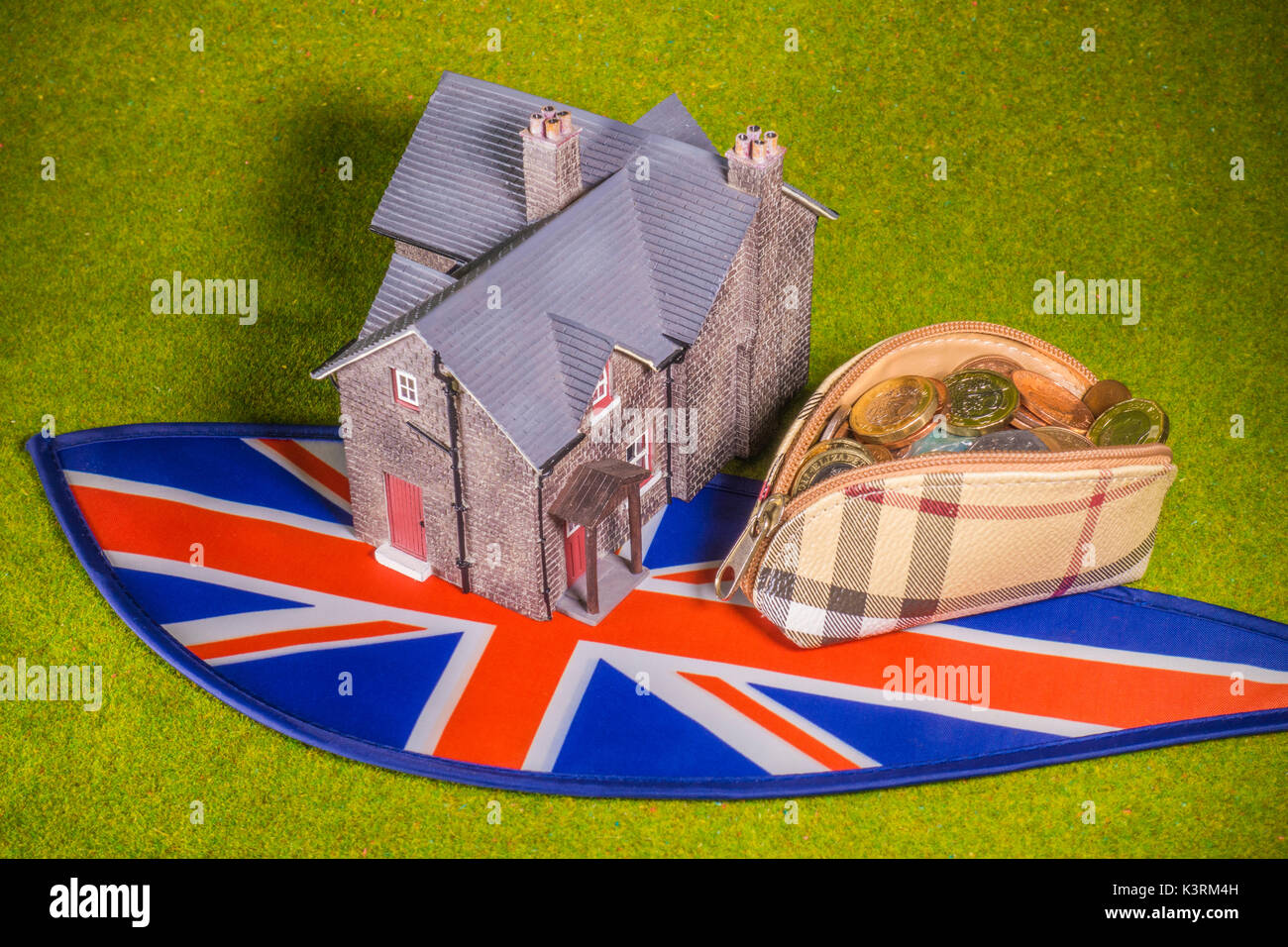 Model house, purse with sterling coins (with new £1) and Union Jack, to depict costs like a UK interest rate rise, home buying, renting, moving, etc. - Stock Image