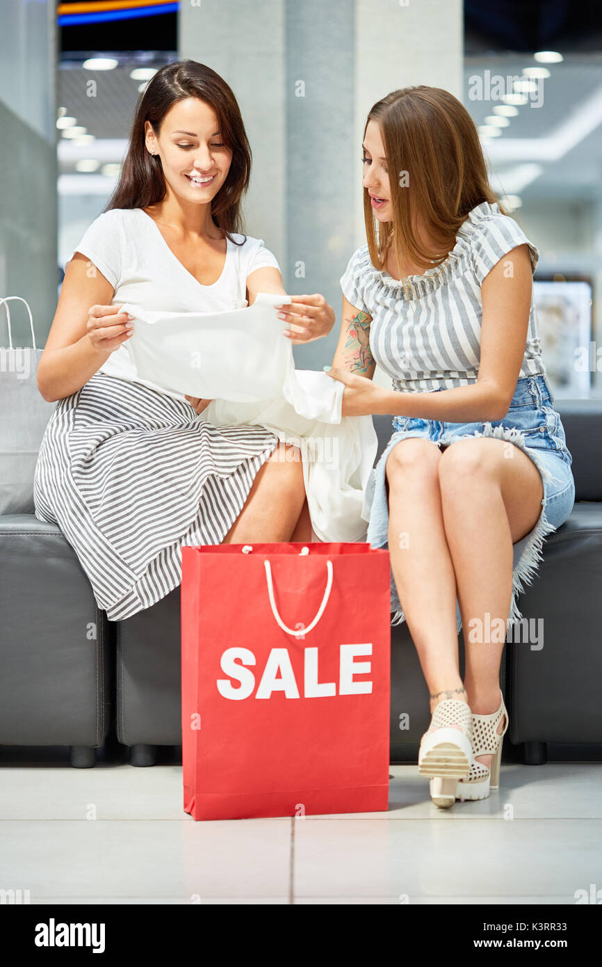 Portrait of two happy women in shopping mall, looking at blouse bought on SALE, red paper bag in foreground - Stock Image