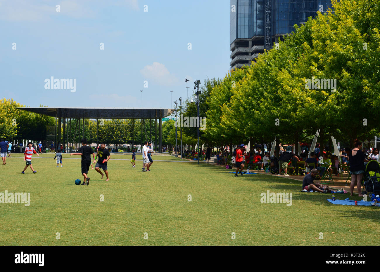 The lawn at Klyde Warren park provides an open space for residents to play and open seating for the music pavilion. - Stock Image