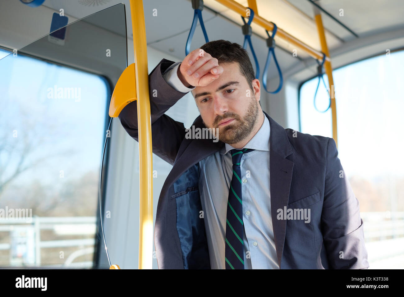 Businessman commuter is traveling and he is sad and tired - Stock Image