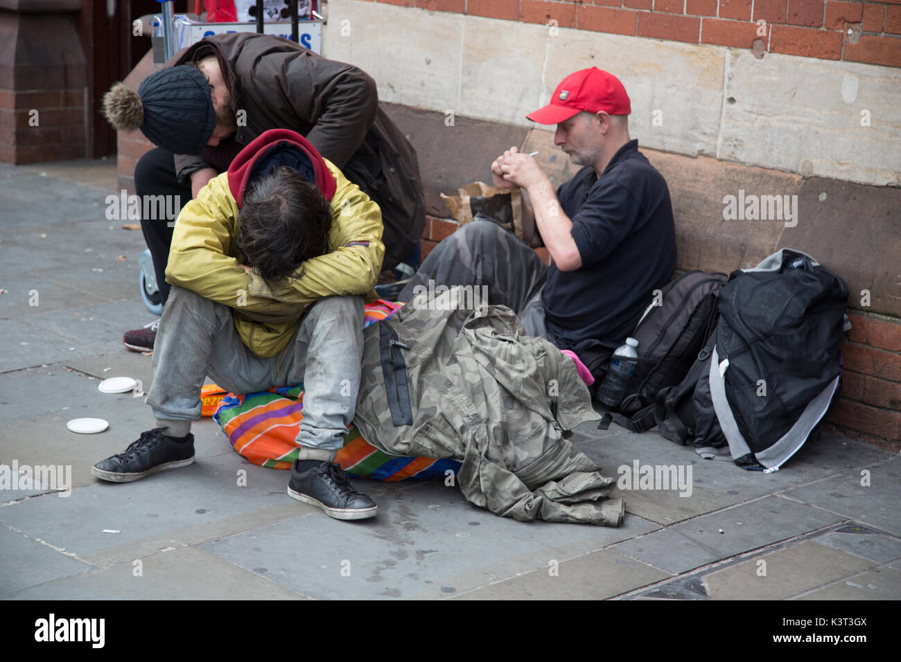 A group of three homeless men sitting on the pavement in London, United Kingdom - Stock Image