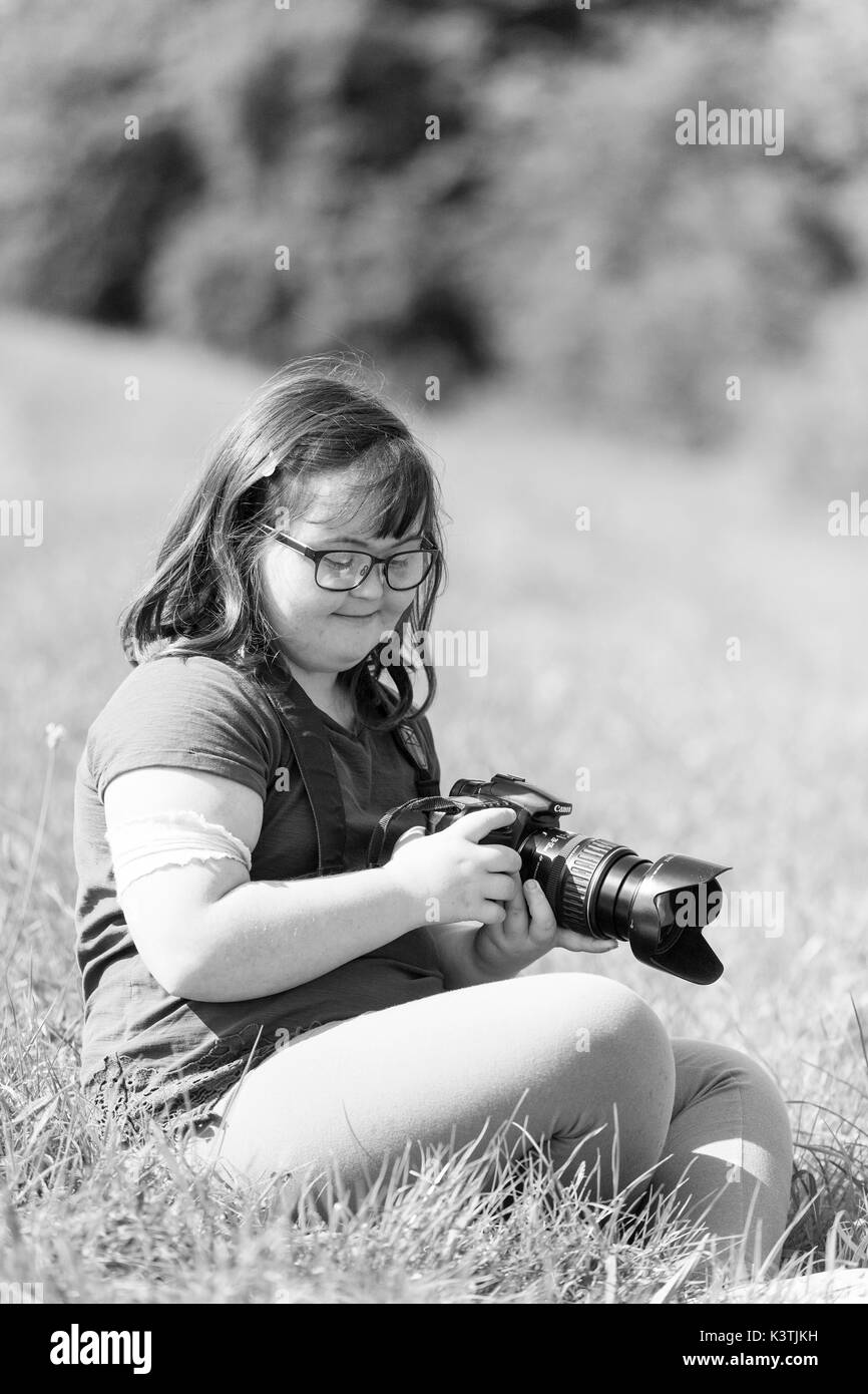 Young girl using a Canon camera. - Stock Image