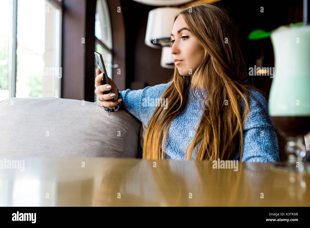 Portret of young female reading sms on the phone in cafe. Toned. Selective focus. - Stock Image