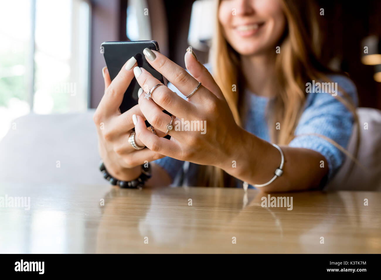 Close up of women's hands holding cell telephone with blank copy space scree for your advertising text message or promotional content, hipster girl watching video on mobile phone during coffee break. Toned. Selective focus. - Stock Image
