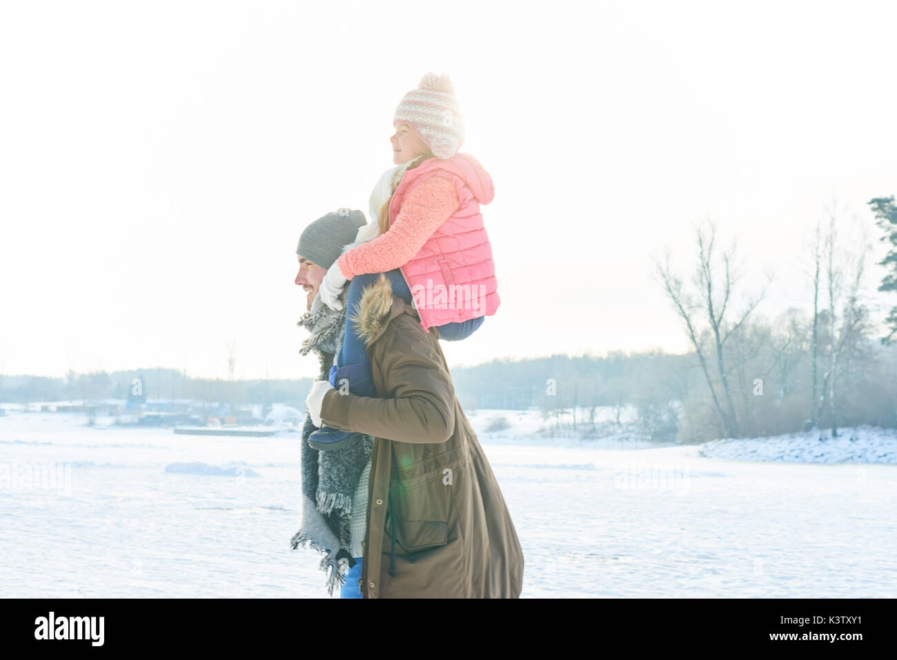 Father with child in winter giving her a piggyback ride - Stock Image