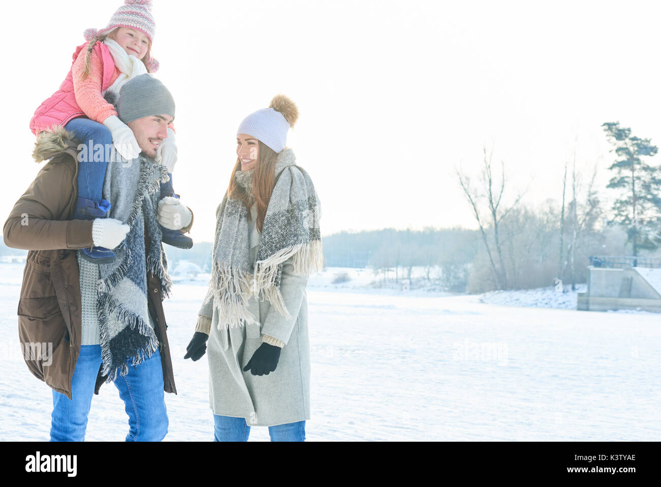 Family with child on winter holidays walking in the nature - Stock Image