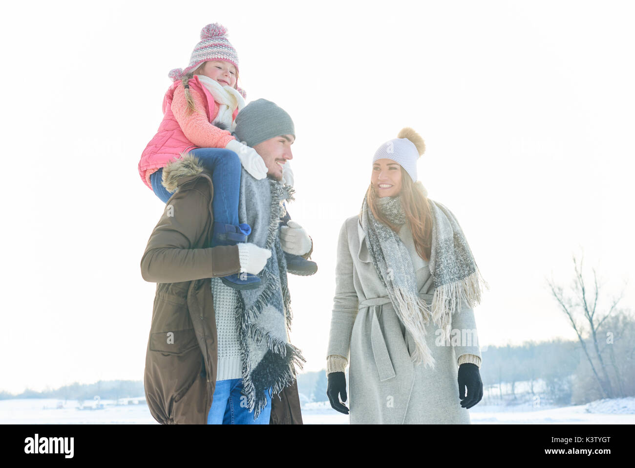 Family on their winter vacation walking in the snow in the nature - Stock Image