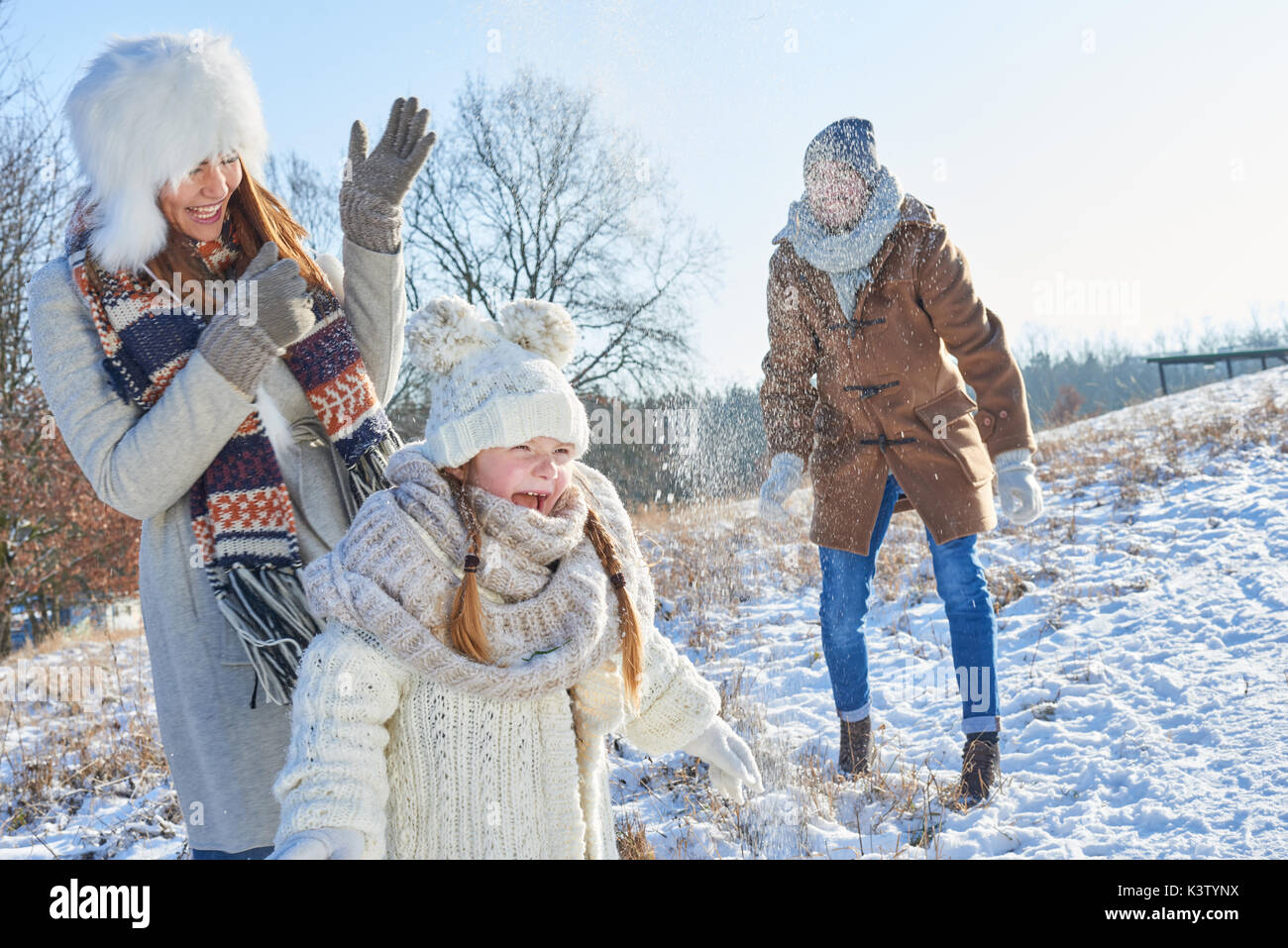 Parents and daughter as family have fun with snowball fight in winter - Stock Image