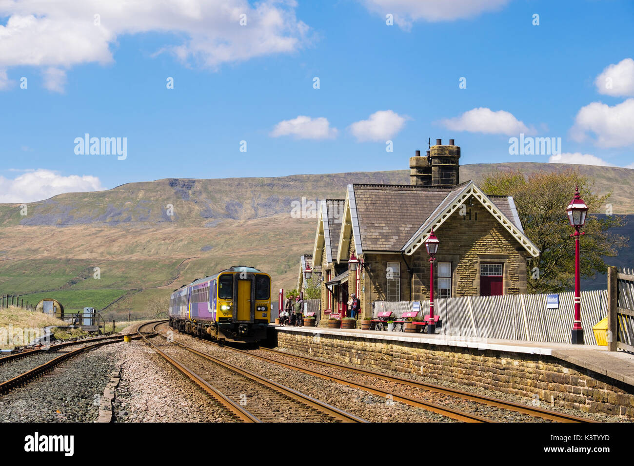 Passengers waiting for train approaching Ribblehead station on Settle to Carlisle railway. Yorkshire Dales National Park North Yorkshire England UK - Stock Image