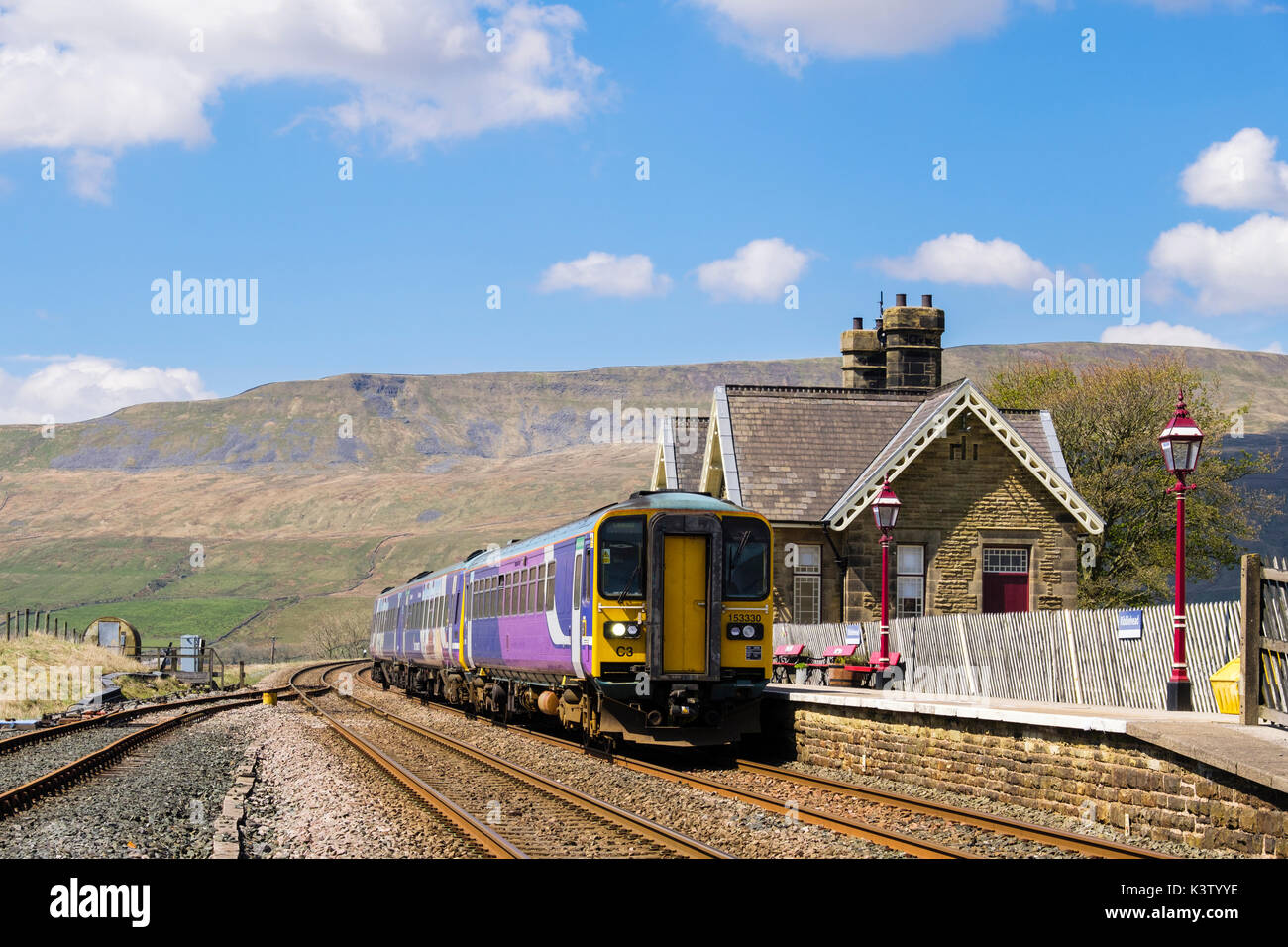 Passenger train stopped at Ribblehead station on Settle to Carlisle railway line. Yorkshire Dales National Park West Riding North Yorkshire England UK - Stock Image