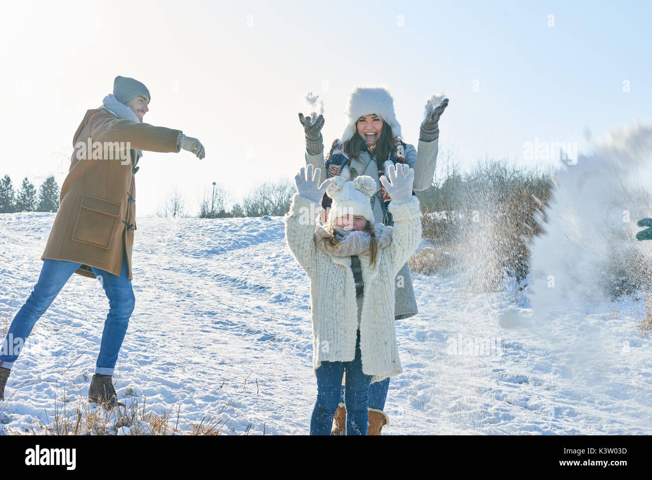 Family in snowball fight having fun with joy in winter - Stock Image
