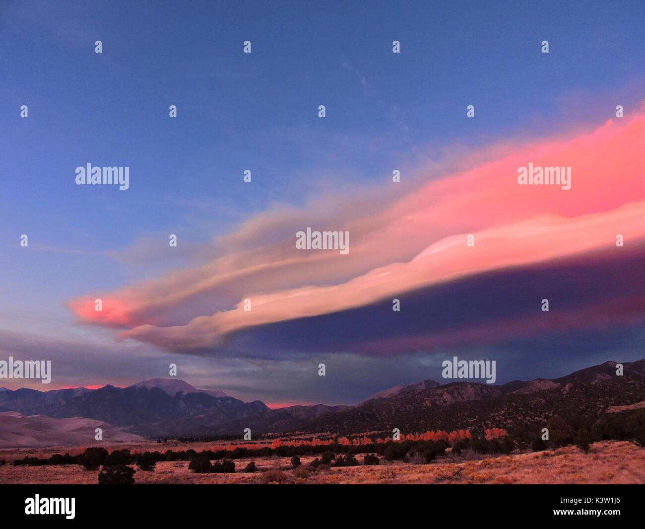 Lenticular clouds form at sunset above the Medano Pass of the Sangre de Cristo Mountains at the Great Sand Dunes National Park and Preserve October 14, 2016 near Westcliffe, Colorado.  (photo by Patrick Myers  via Planetpix) - Stock Image