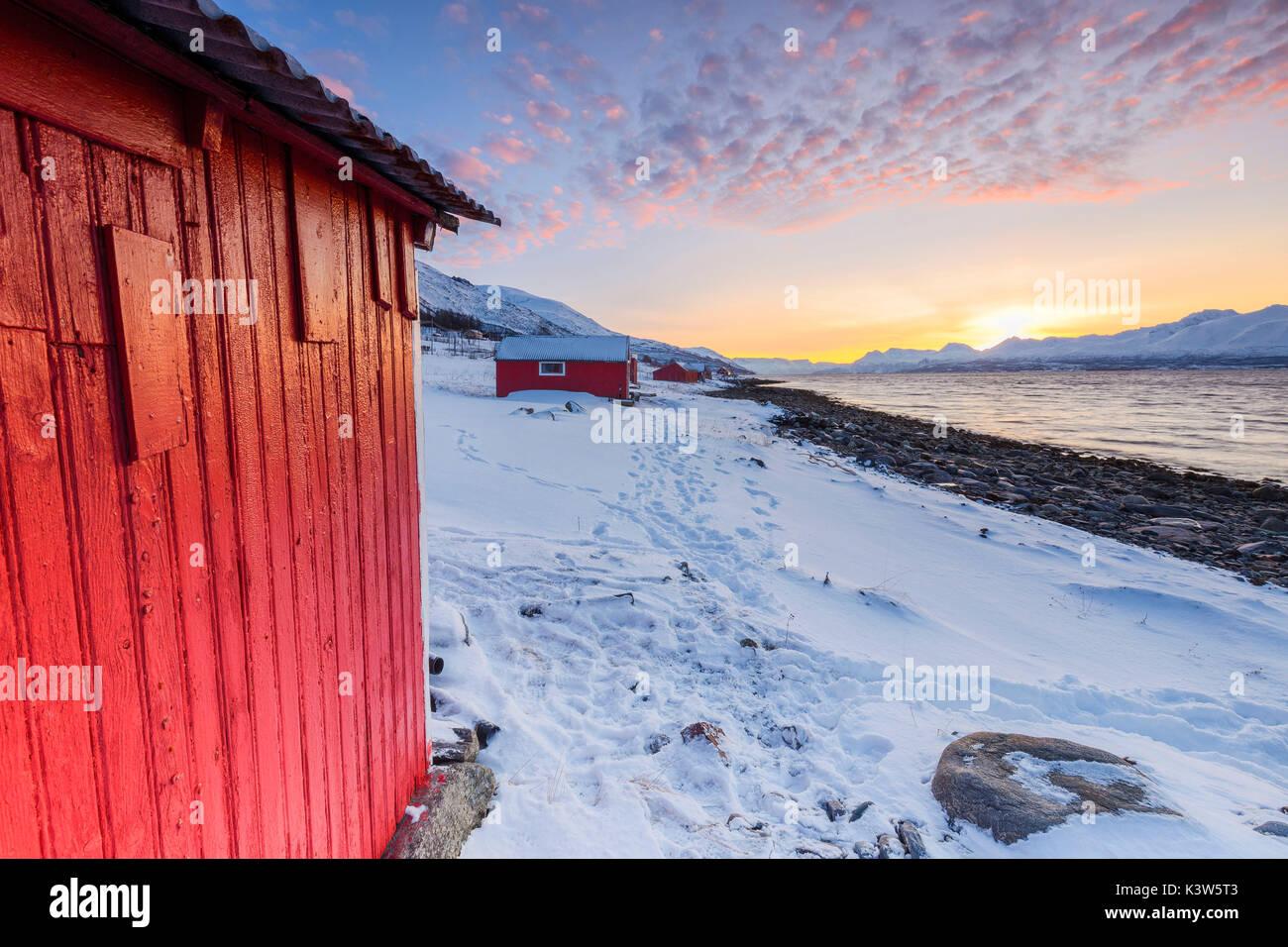 Sunset among the fishermen's houses overlooking the fjord. Nordmannvik, Kafjord, Lyngen Alps, Troms, Norway, Lapland, Stock Photo