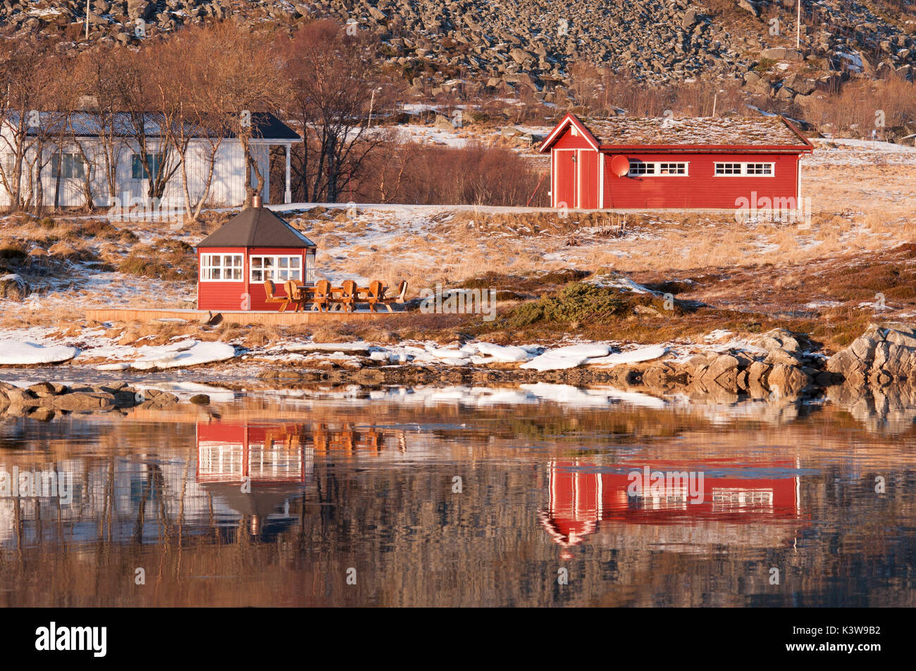 Some rorbuer reflected on the water of the near fiord in the Lofoten Islands, Norway. - Stock Image