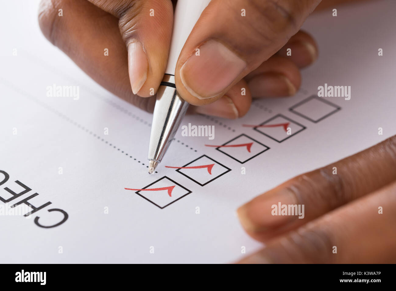 Close-up Of Person's Hand Marking On Checklist Form With Red Pen - Stock Image