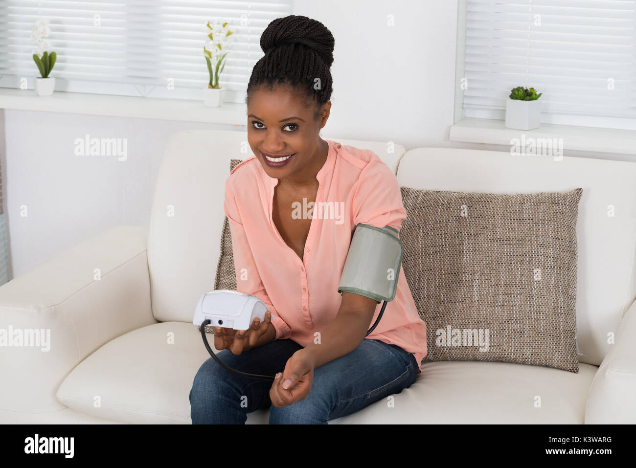 Young African Woman Checking Blood Pressure At Home - Stock Image