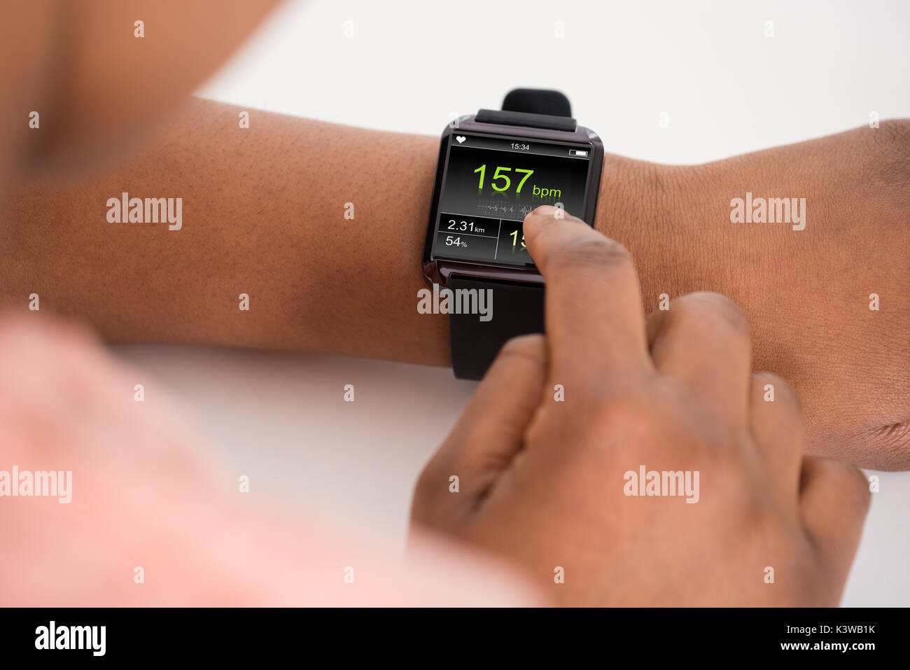Close-up Of Hand Wearing Smartwatch Showing Heartbeat Rate Stock Photo