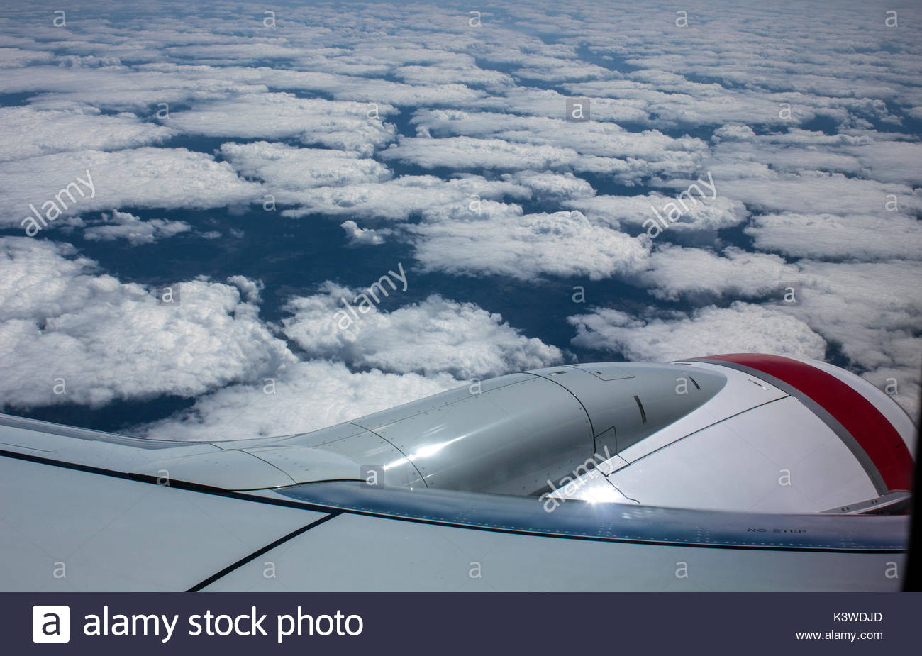 View from the window of a commercial airliner flying above clouds. - Stock Image