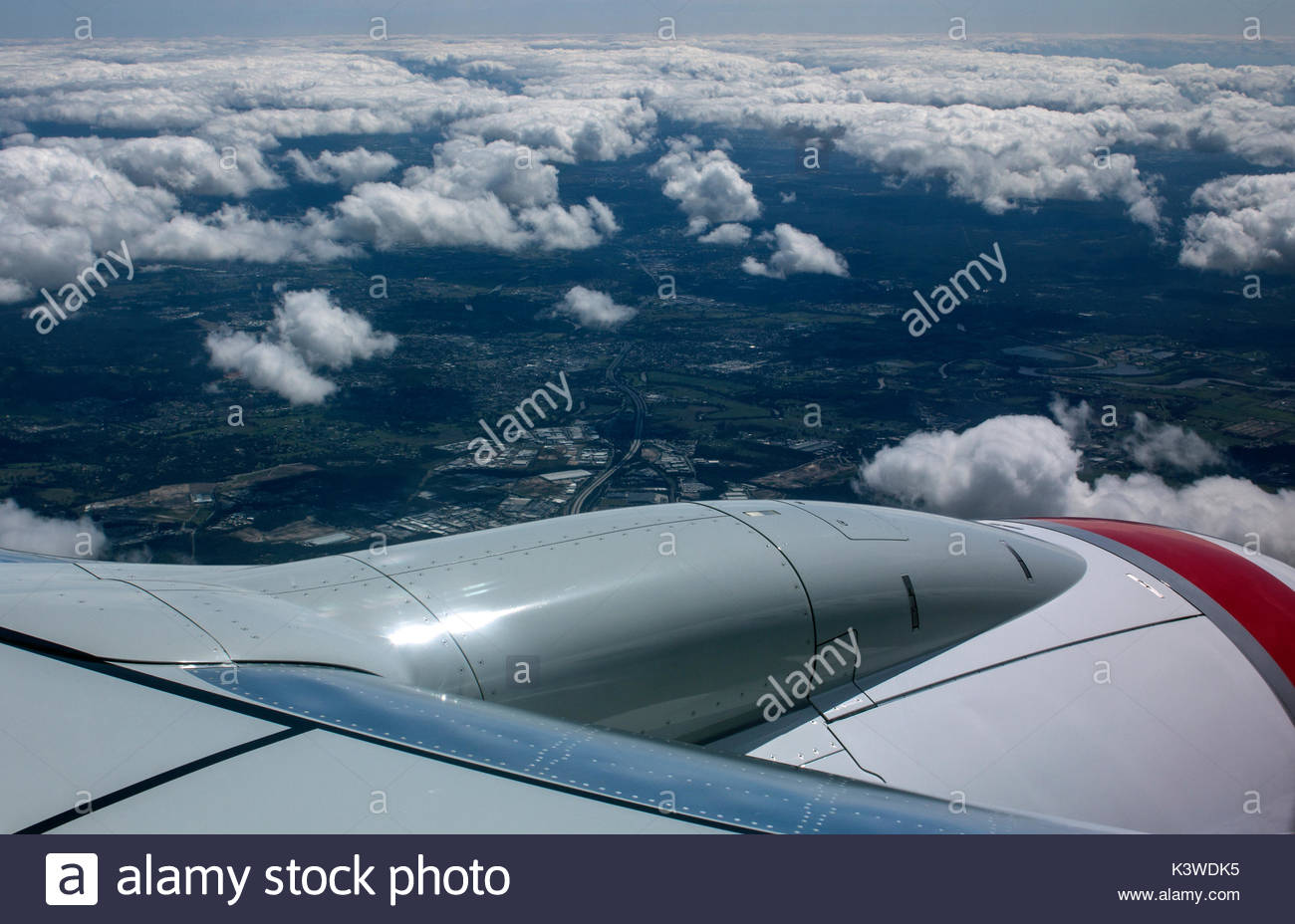 View looking over the jet engine and down through the clouds from the window of a commercial airliner. - Stock Image
