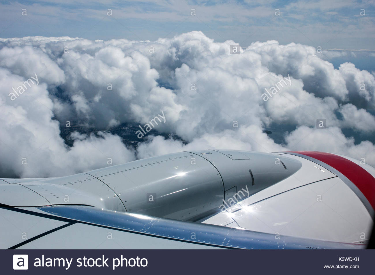 View looking over the jet engine from the window of a commercial airliner during descent. - Stock Image