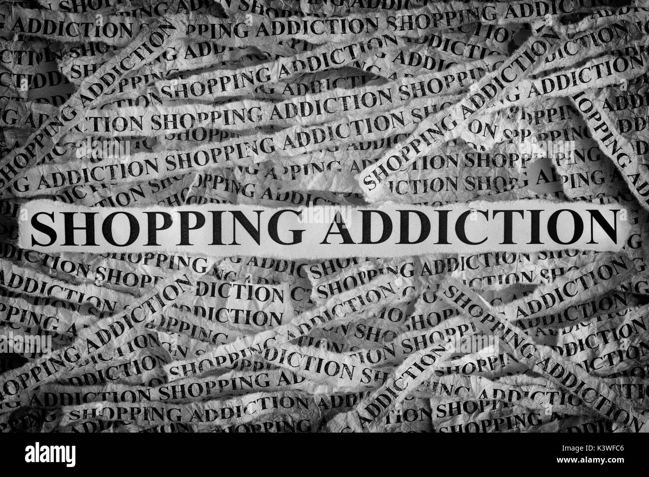 Shopping Addiction. Torn pieces of paper with the words Shopping Addiction. Concept Image. Black and White. Closeup. - Stock Image
