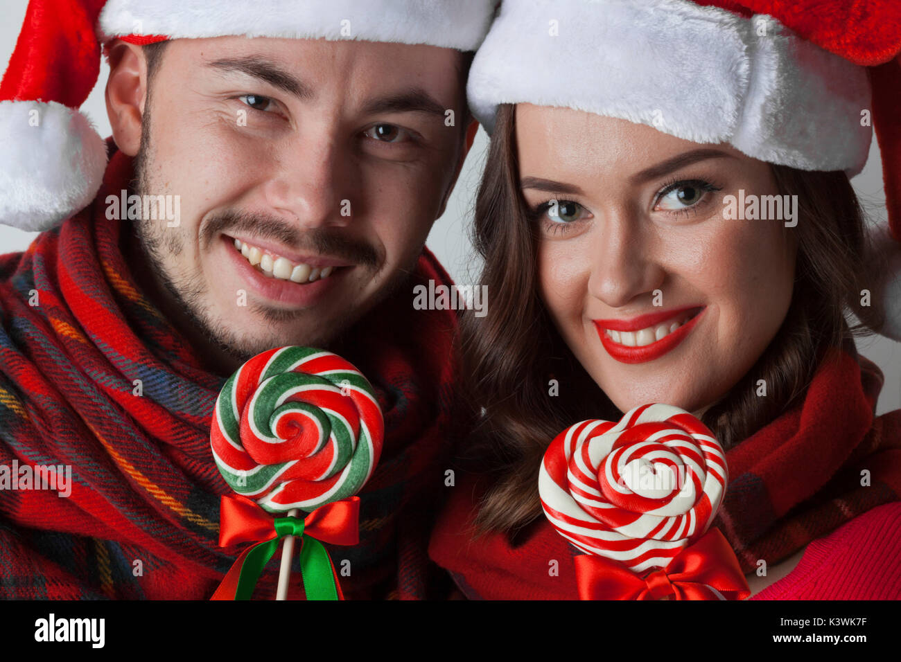 Young Happy Funny Couple In Christmas Santa Hats With Lollipops