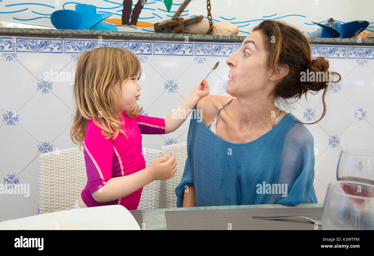 funny scene of three years old blonde child putting spoon in the face of woman mother sitting in restaurant - Stock Image