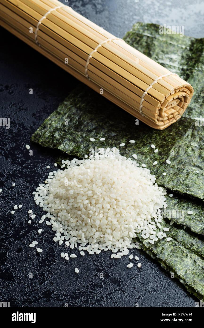 Green nori sheet , rice and bamboo mat on black table. - Stock Image