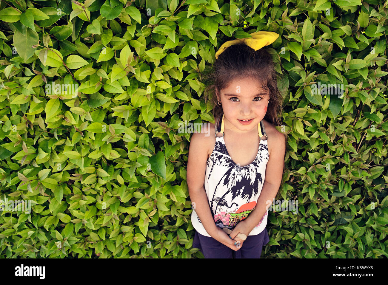 Little girl with green leaves - Stock Image