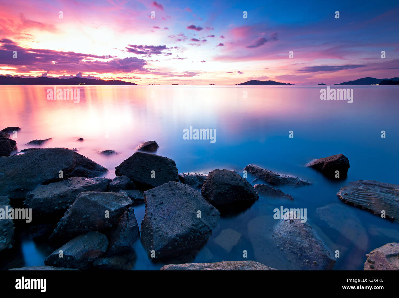 Vibrant and colorful sunset in Kota Kinabalu beach, Tanjung Lipat in Sabah Borneo, Malaysia. - Stock Image