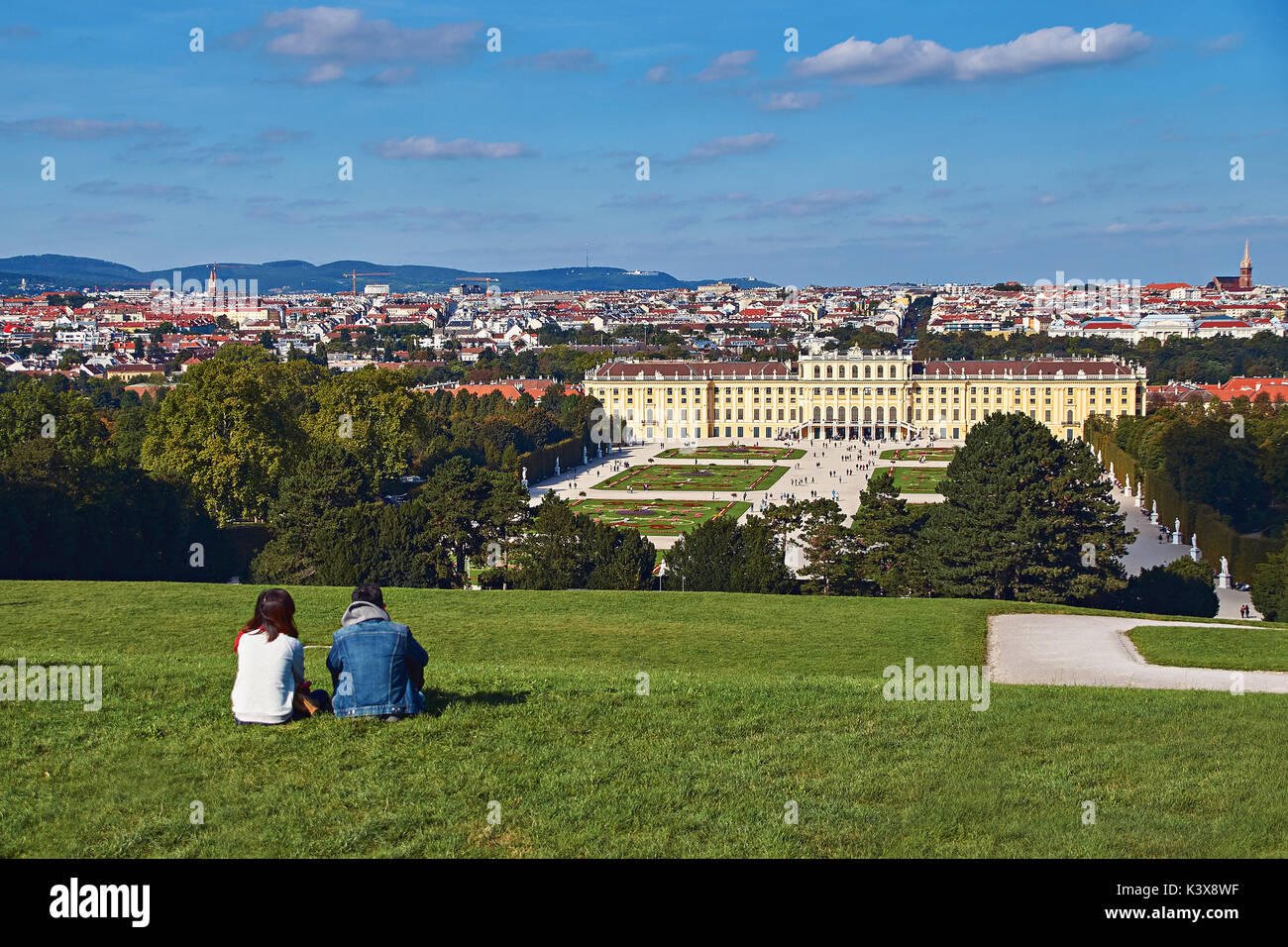 Vienna, Austria - September 24, 2014: Couple of tourists sitting on the grass with the view of Schonbrunn palace Stock Photo