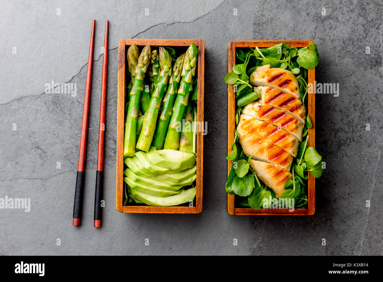Healthy lunch in wooden japanese bento box. Balanced healthy food grilled chucken and avocado with asparagus and green salad. Top view, slate gray bac - Stock Image