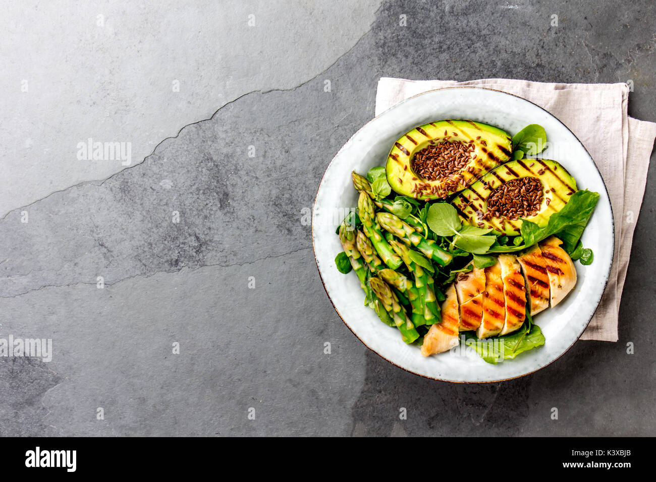 Healthy grilled chicken, grilled avocado and asparagus salad with linen seeds. Balanced lunch in bowl. Gray slate background. Top view. - Stock Image