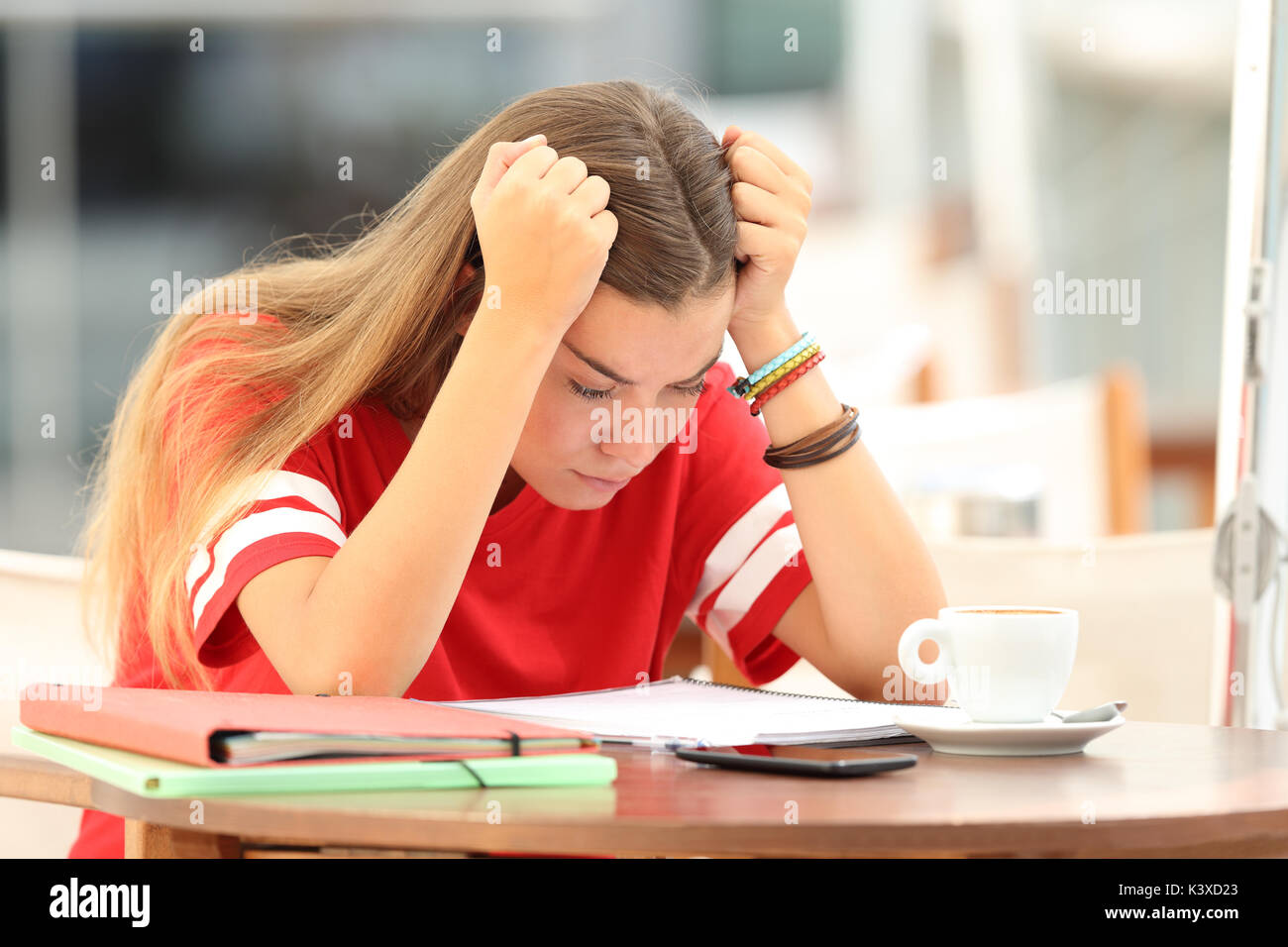 Single frustrated student girl trying to understand notes sitting in a bar Stock Photo