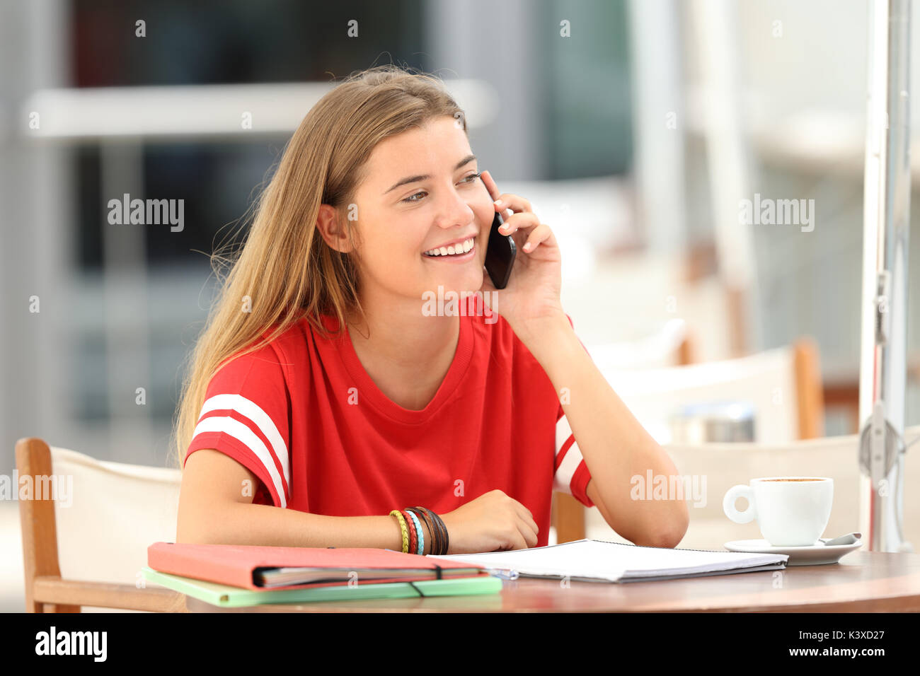 Happy single student talking on phone sitting in a bar - Stock Image