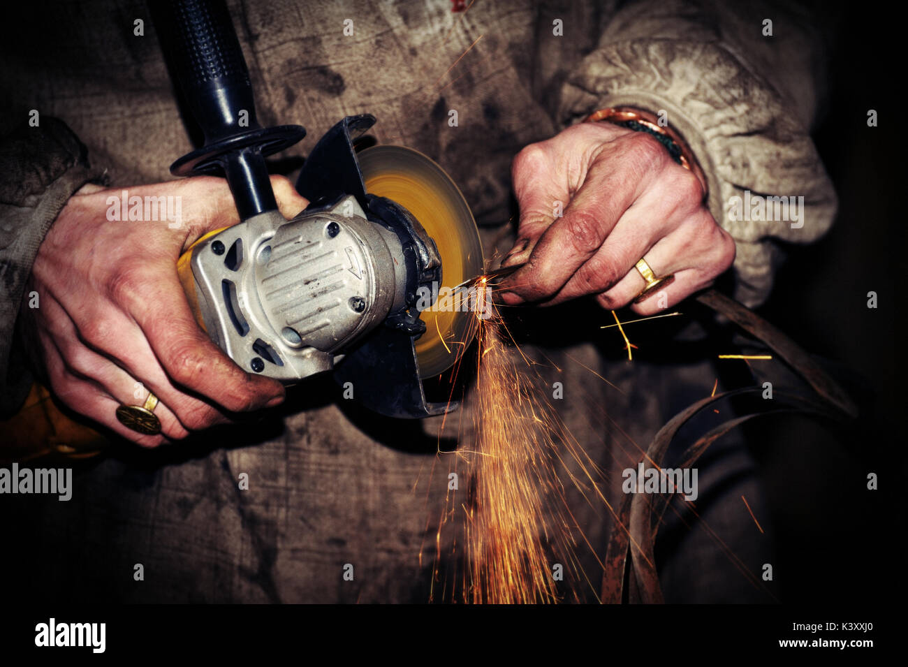 angle grinder in hand working - Stock Image