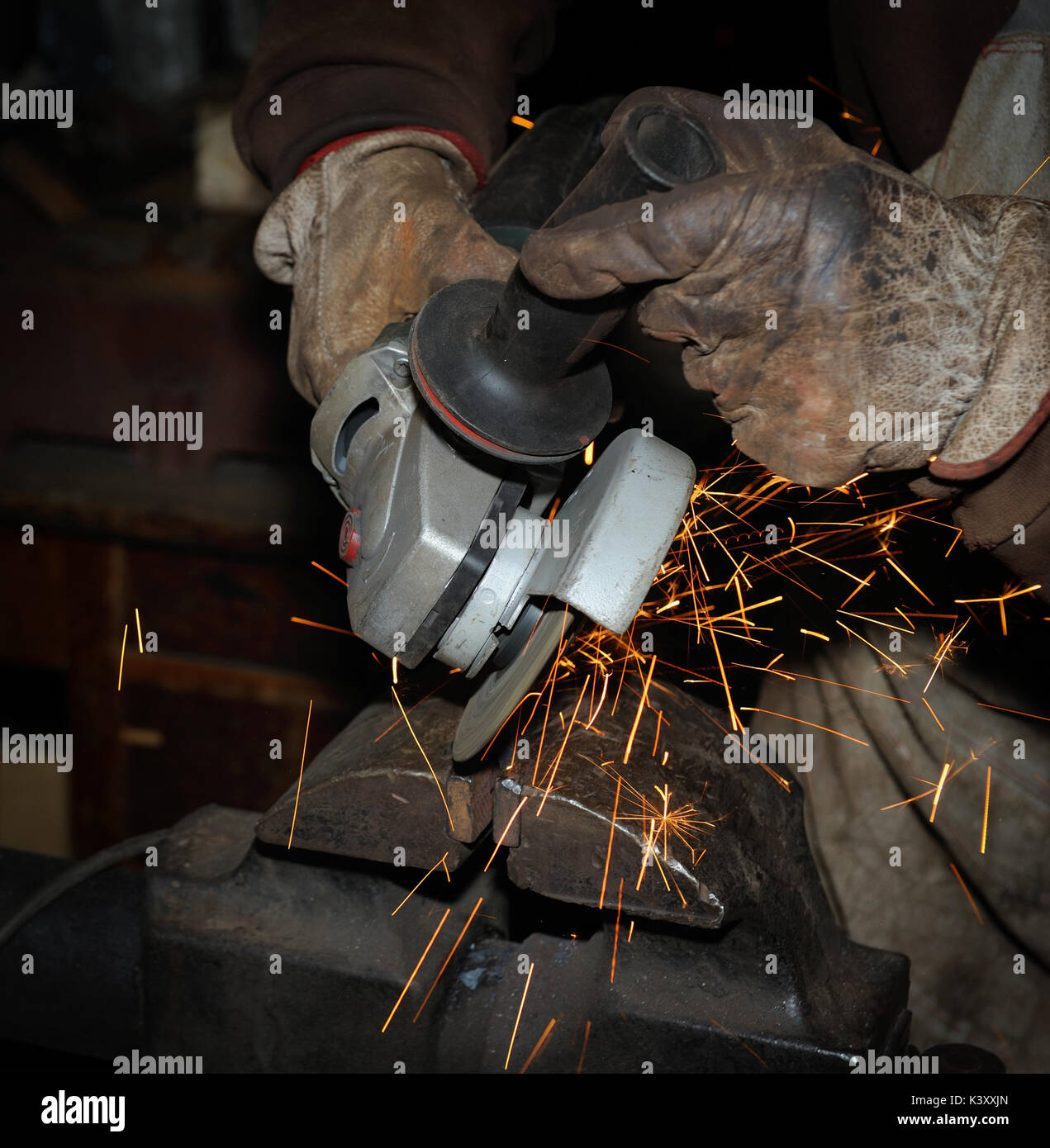 Heavy industry worker cutting steel with angle grinder - Stock Image