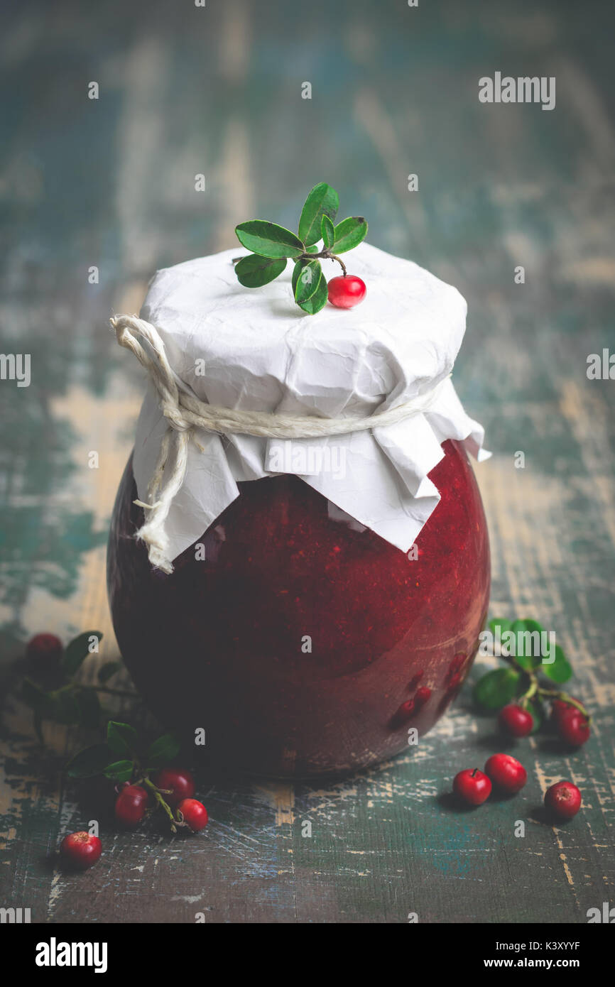 Lingonberry jam in jar and fresh berries. Selective focus  - Stock Image
