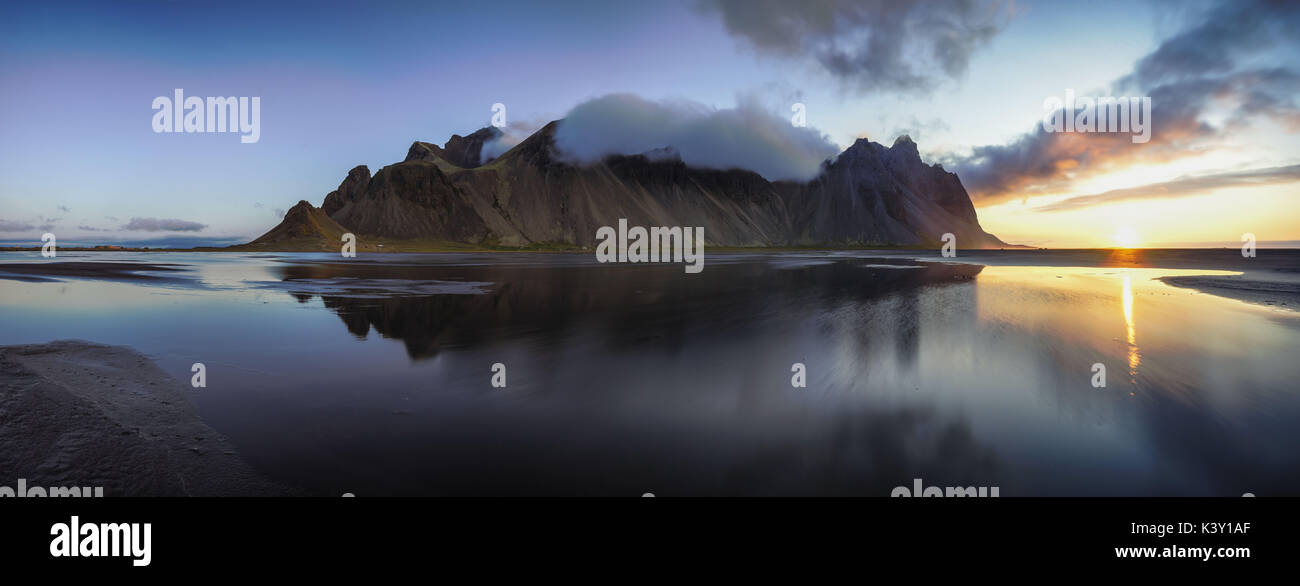 Panoramic view of Vestrahorn mountain reflected in shallow water at sunrise. - Stock Image