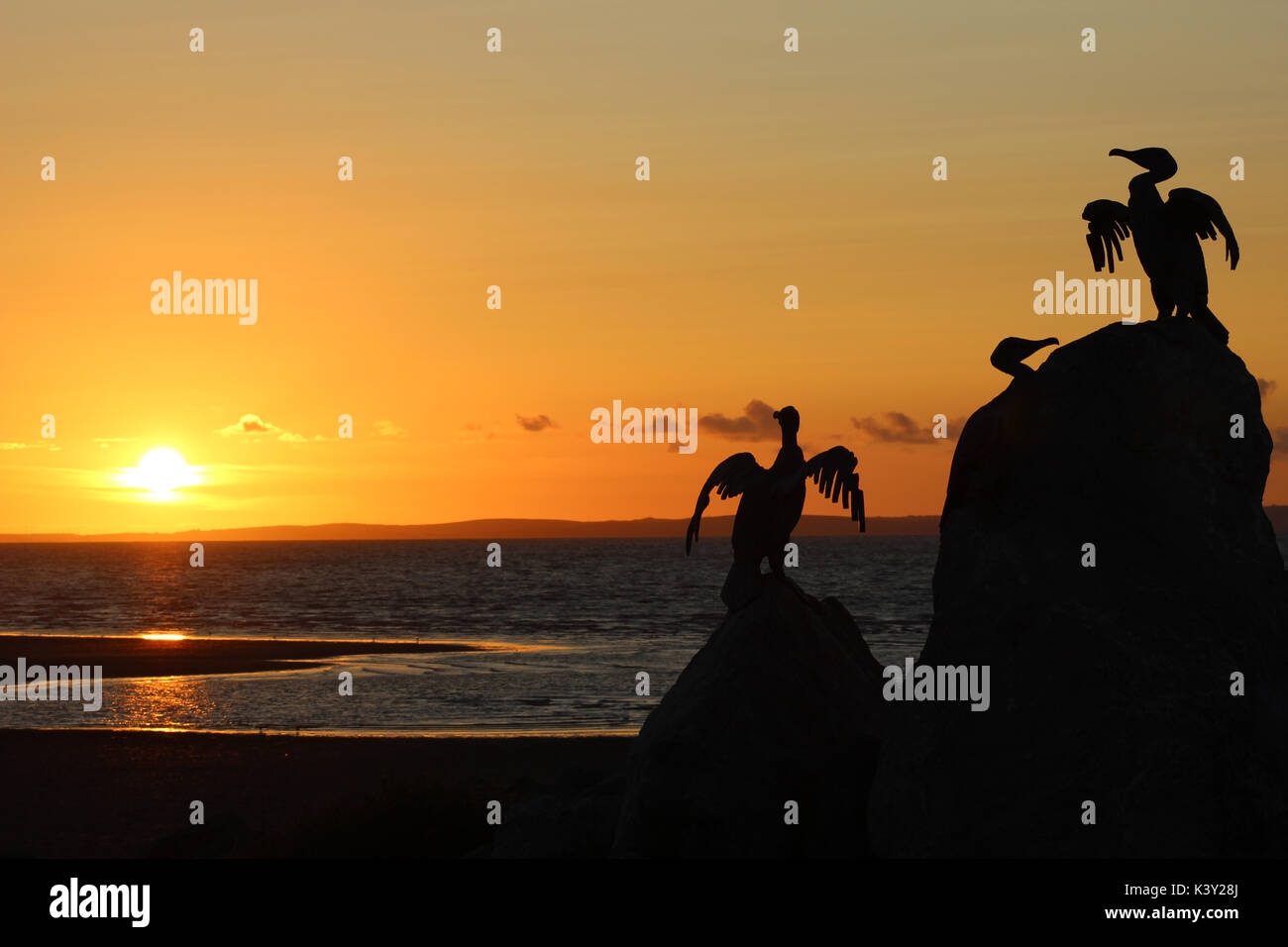 Sunset over Morecambe Bay from the Stone Jetty in Morecambe, Lancashire, England with silhouettes of sculptures of cormorants in the foreground. - Stock Image