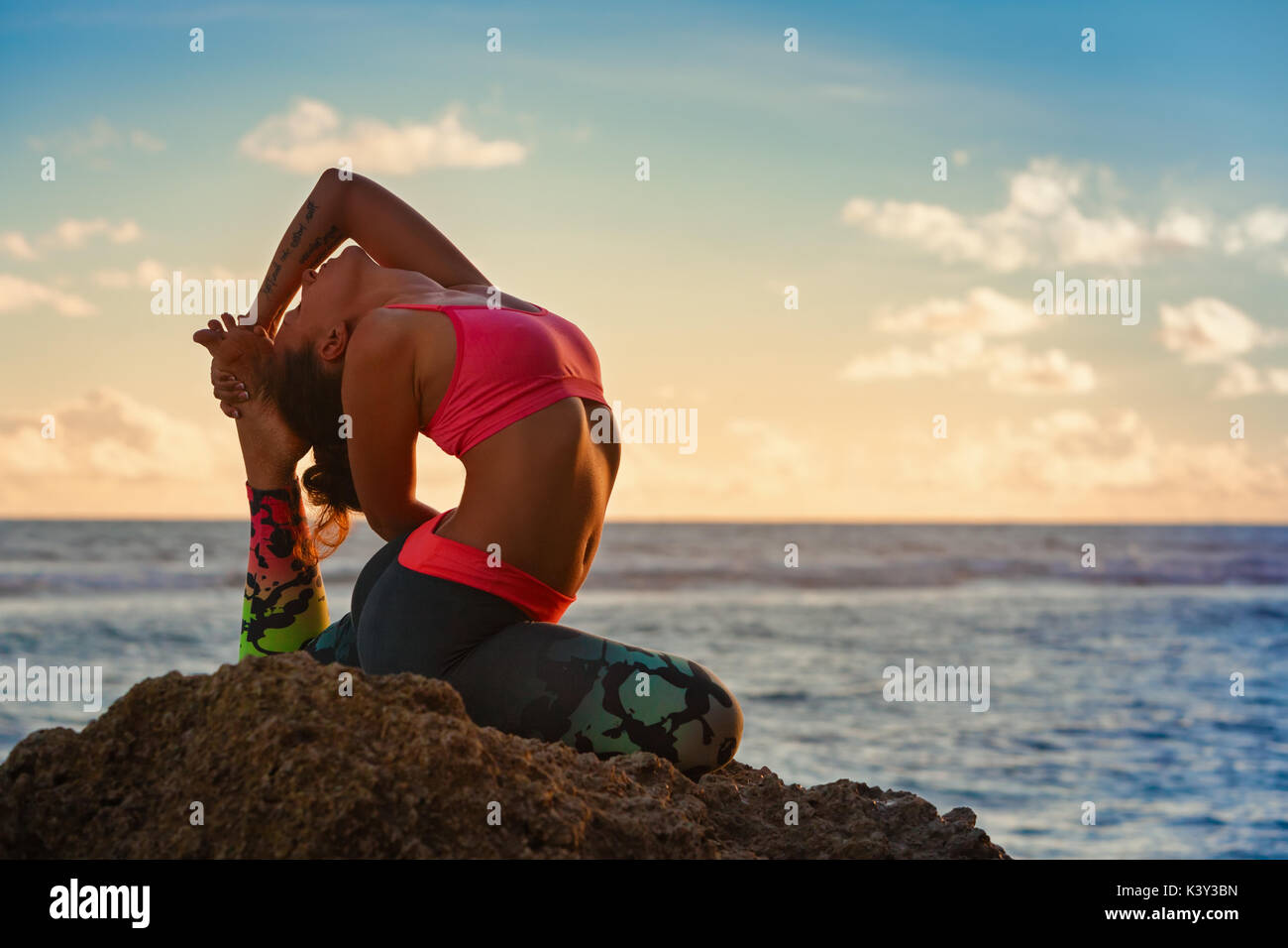Meditation on sunset sky background. Young active woman sit in yoga pose on beach rock, stretching to keep fit and health. Healthy lifestyle, fitness - Stock Image