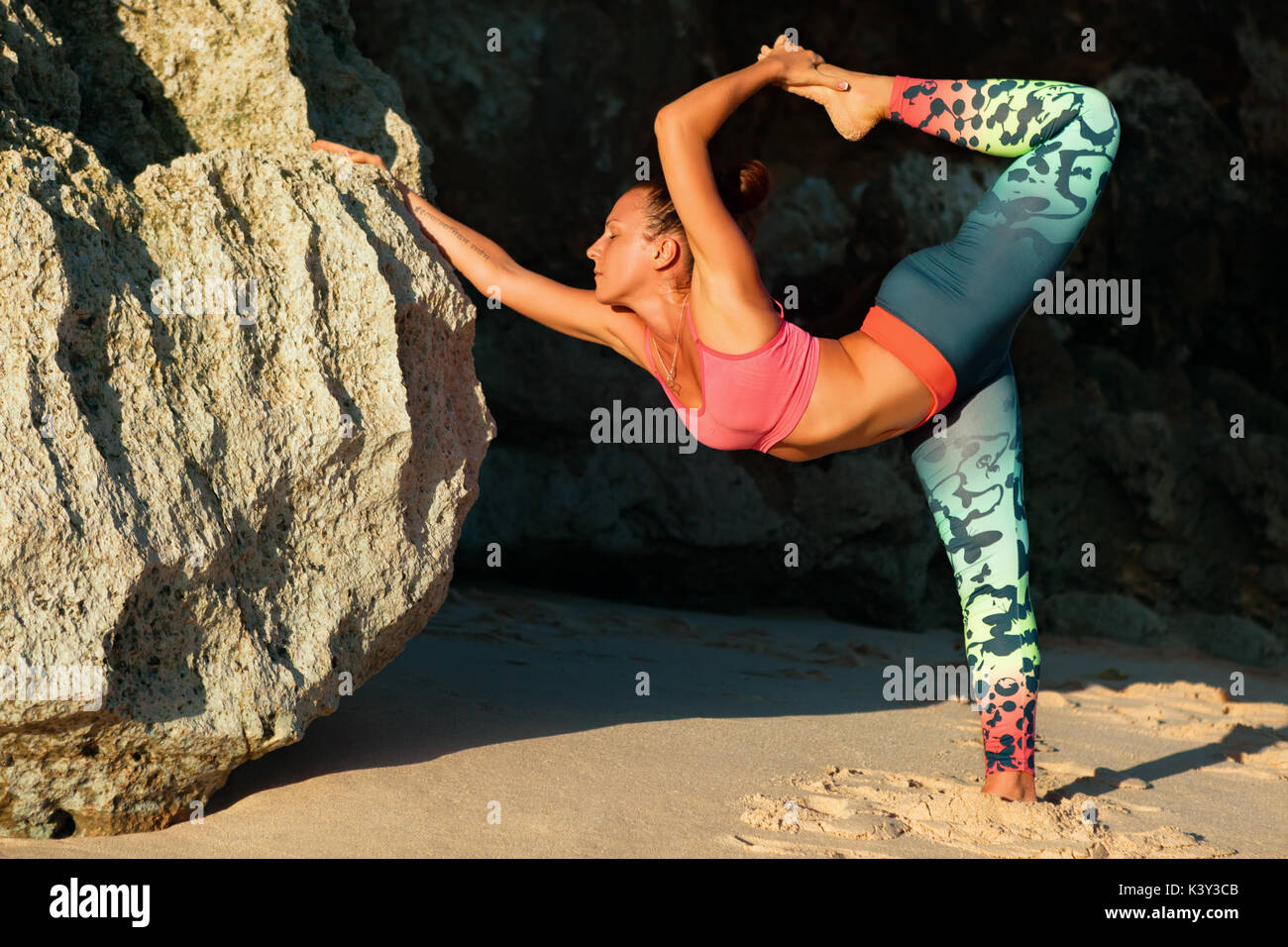 Meditation on rock background. Young active woman stand in yoga pose on beach rock, stretching to keep fit and health. Healthy lifestyle, fitness. - Stock Image