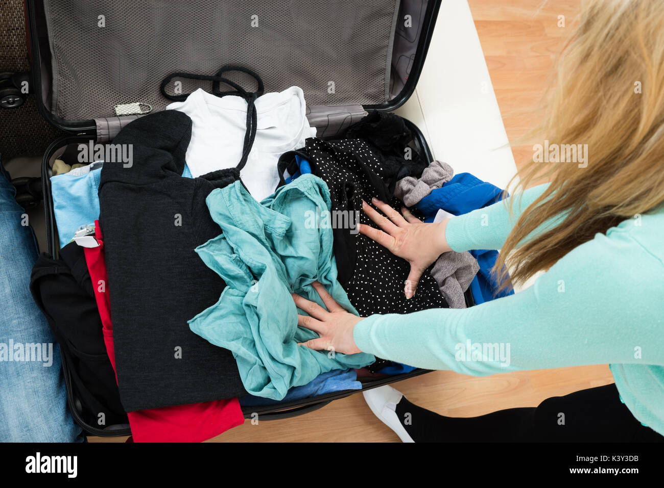 High Angle View Of Woman Packing Clothes In Suitcase - Stock Image