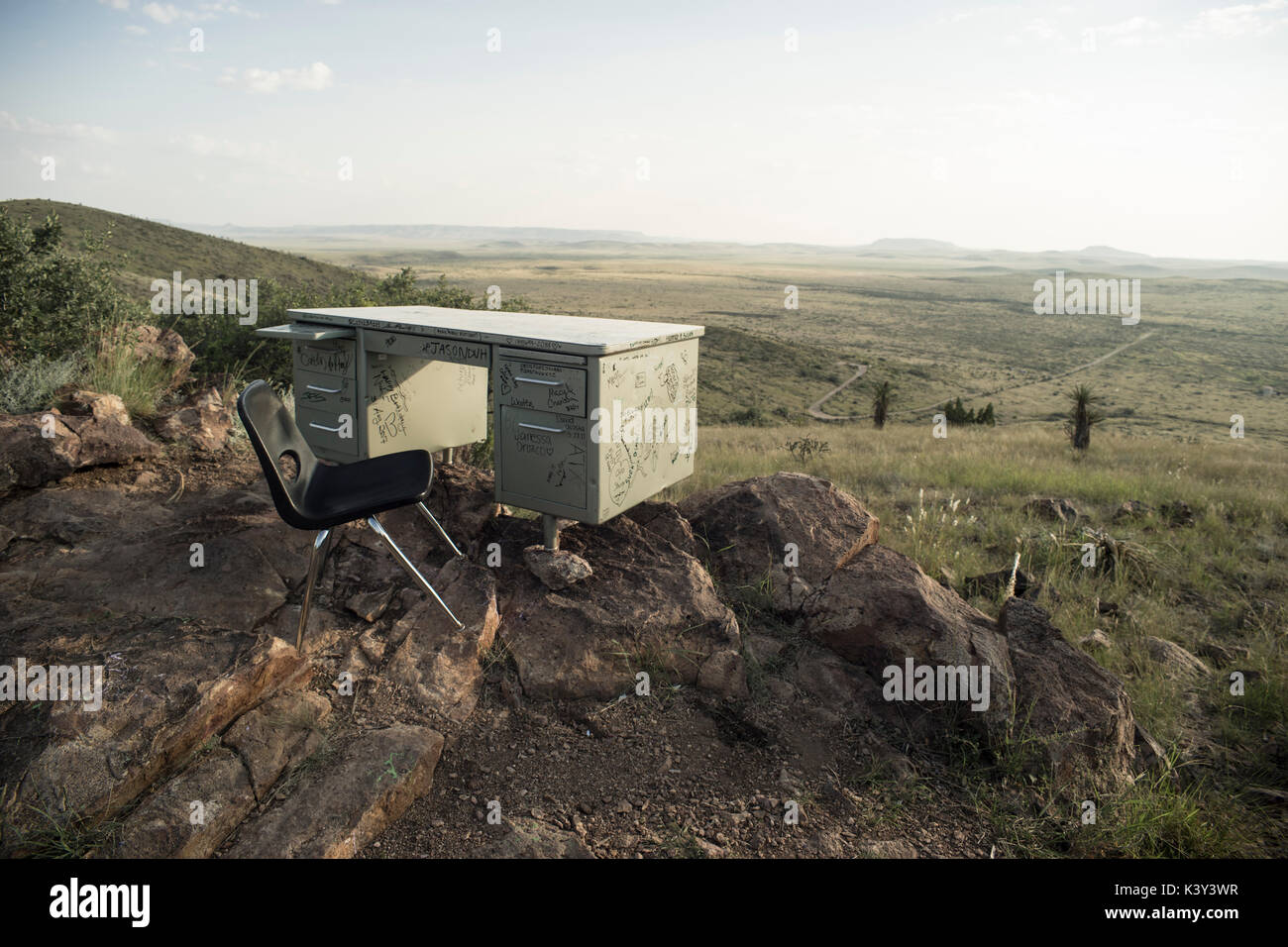 Desk and chair brought atop of Hancock Hill in Alpine, Texas, a a prank by students of Sul Ross University. - Stock Image