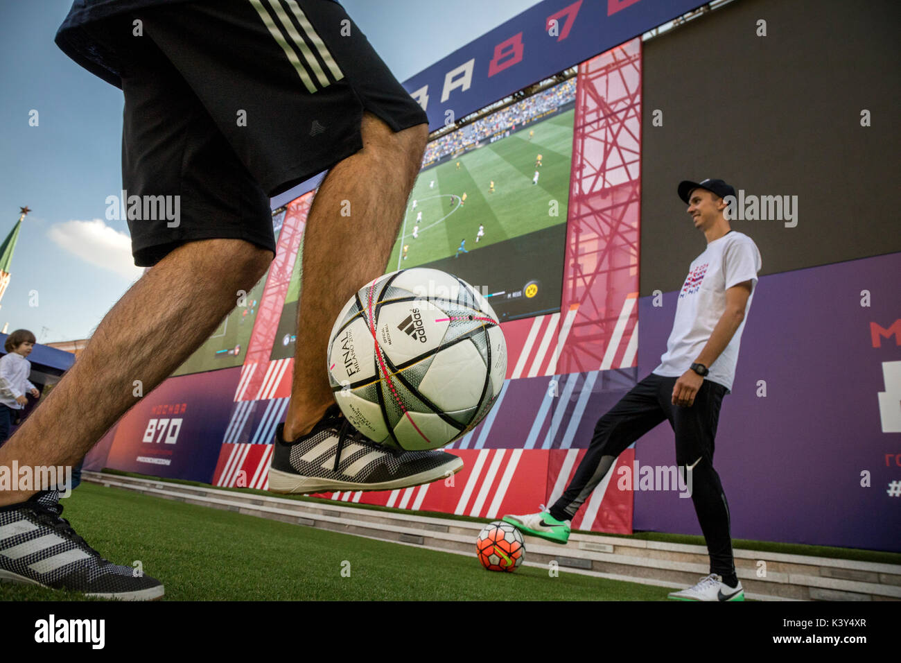 People play football on the site of the festival 'Moscow-870' with big screen FIFA 17 computer game on the Manezhnaya Square in Moscow, Russia - Stock Image